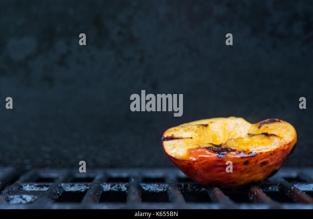 Single Grilled Peach on Right With Copy Space over grills - Stock Image