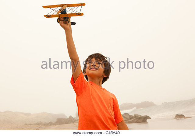 Boy wearing orange t shirt playing with toy plane - Stock-Bilder