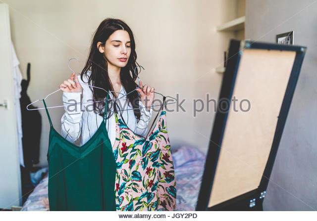 Young woman standing in front of mirror, holding up clothes, deciding what to wear - Stock Image