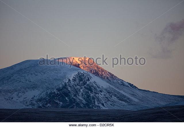 First light on Svanåtindan at Dovrefjell, Norway. - Stock-Bilder