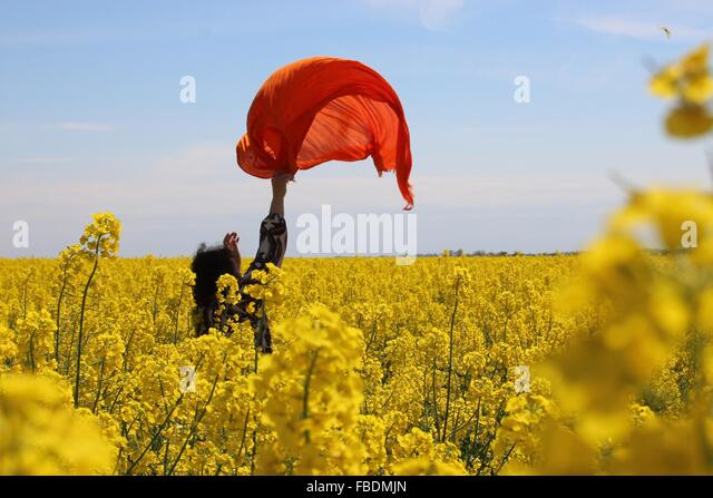 Woman With Scarf In Canola Field - Stock Image