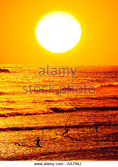 Wind surfers launch boards, late afternoon ocean waves  toward a huge  setting  sun across the water, Pacific Ocean - Stock Image