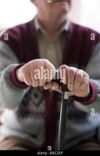 elderly man oap old age pensioner hands clutching walking stick at home - Stock Image