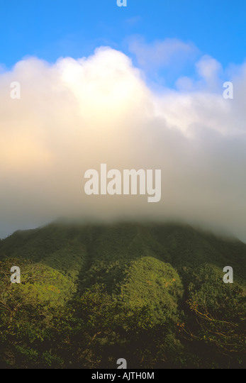 Mount Nevis peak, caribbean, Nevis, brooding cloud cover at the summit, clear day blue sky background, island symbol - Stock Image
