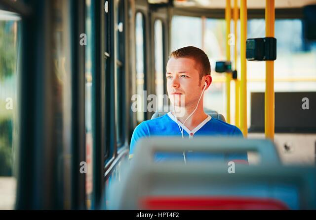 Loneliness man is wearing headphones and listening to music. Everyday life and commuting to work by public transportation. - Stock Image