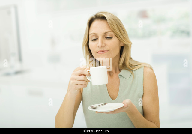 Woman holding coffee cup, smiling - Stock-Bilder