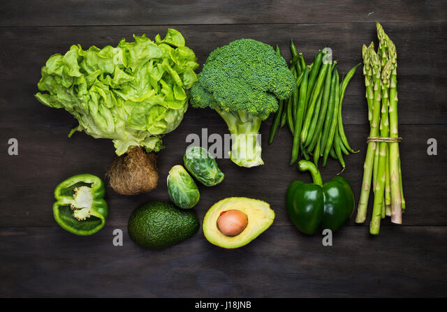 Fresh green organic vegetables on black wooden vintage table.Top view - Stock Image