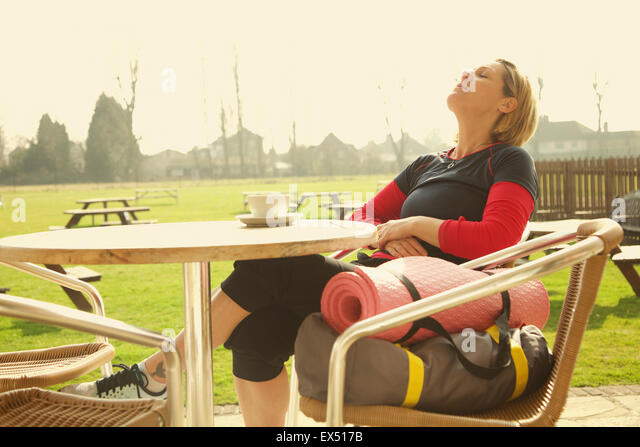 Woman Wearing Exercise Clothing Relaxing at Outdoor Cafe - Stock Image