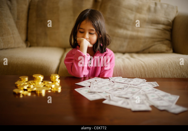 Girl makes investment decision between chocolate gold coins and paper US dollars - Stock Image