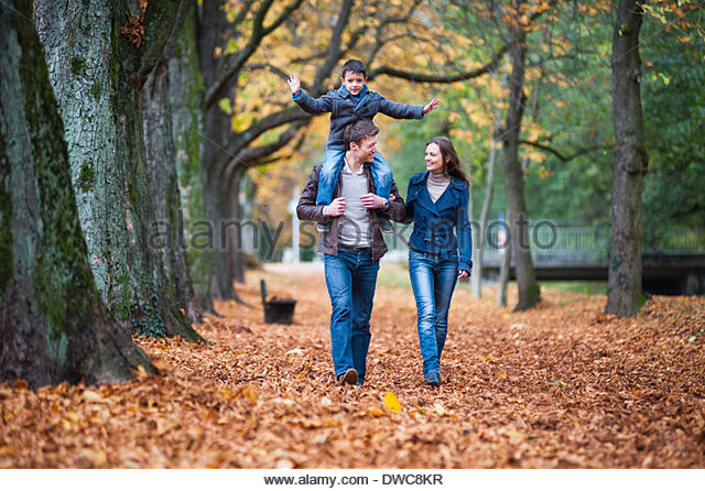Family strolling through autumn leaves in park - Stock Image