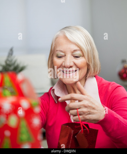 Senior Woman With Christmas Gift - Stock Image