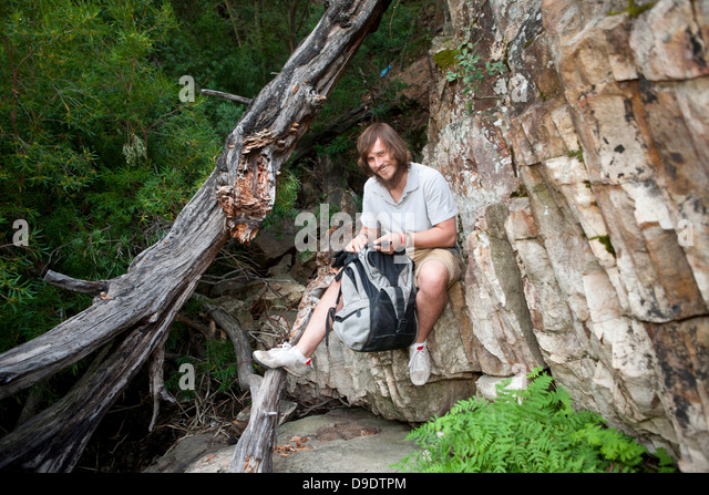 Portrait of young male hiker photographing sitting on rock - Stock Image