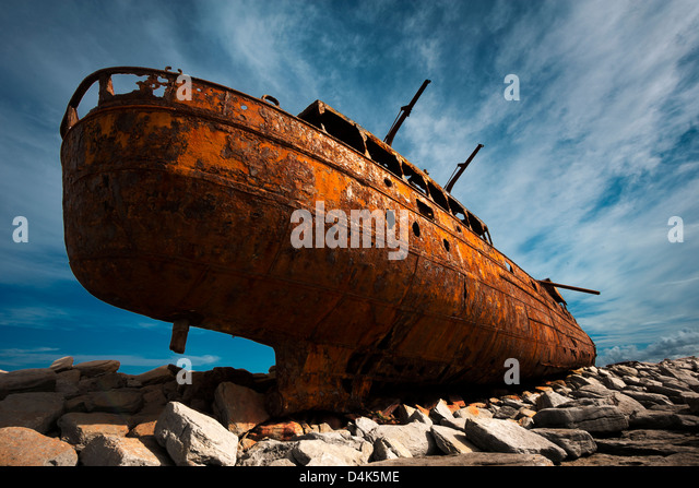 Rusted shipwreck on rocky beach - Stock Image
