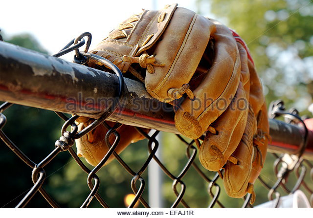 Baseball glove on top bar of chainlink fence - Stock-Bilder