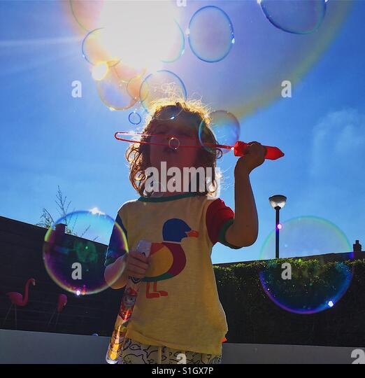 Boy blowing bubbles in sunny garden - Stock-Bilder