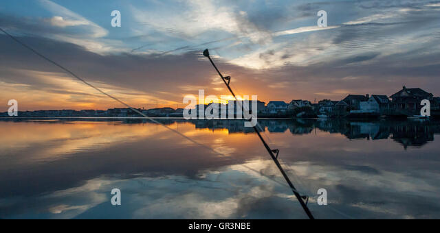 A fishing rod is silhouetted at sunrise in Stone Harbor, New Jersey United States   sunset boating on the bay   - Stock Image