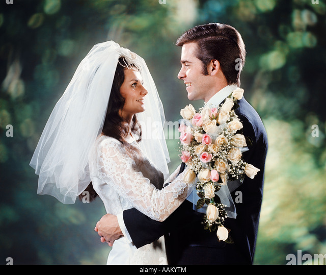 1970s BRIDE GROOM HUGGING EMBRACE FACE TO FACE BRIDAL BOUQUET COUPLE MAN WOMAN - Stock Image
