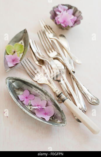 Pink hydrangeas, vintage baking tins and cutlery - Stock Image