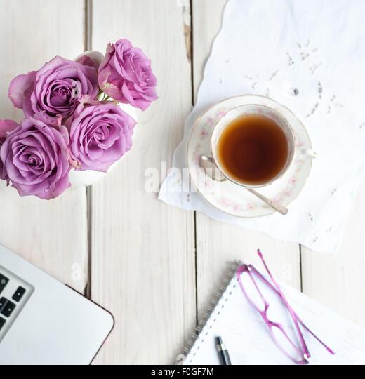 working at home tea break with roses laptop notebook glasses - Stock-Bilder