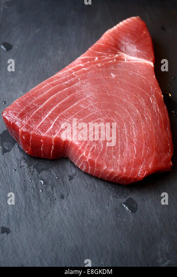 Raw Tuna steak on slate - Stock Image