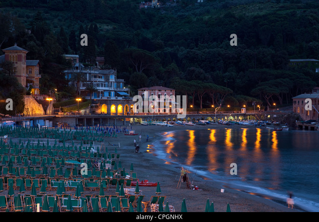 Lights reflect off the sea in the evening light of Levanto, Italy. - Stock Image