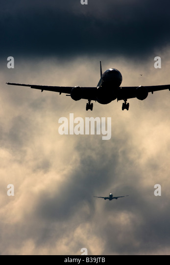 Commercial airplanes queuing up to land while wake turbulence forms behind . London Heathrow Airport UK - Stock Image