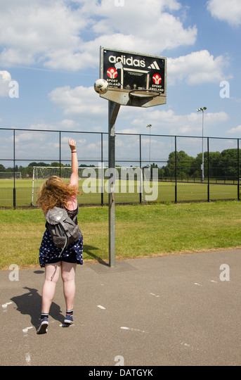 Teenage girl playing netball in the park - Stock Image