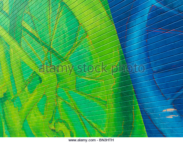Abstract colorful green blue mural graffiti on a brick wall - Stock Image