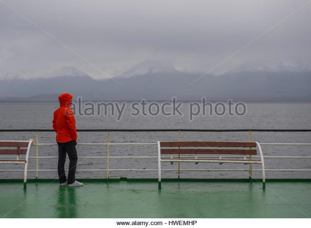 Woman looks out to misty mountains from a ship in the Patagonian fjords, Chile - Stock-Bilder