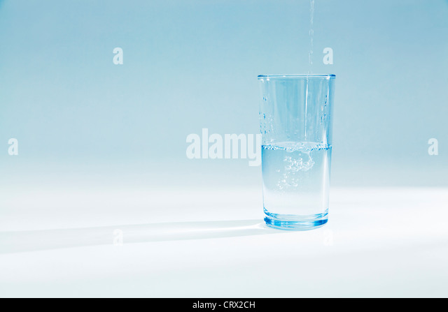 Water pouring into a half full glass tumbler in a blue light - Stock Image
