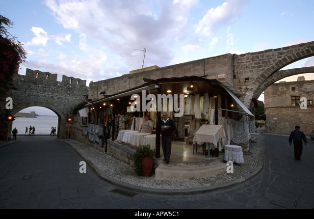 Greece Europe Isle of Rhodes Old Town shopkeeper hand made embroidery medieval gate - Stock Image