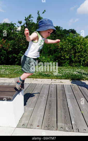 A two year old boy jumping from a bench - Stock Image