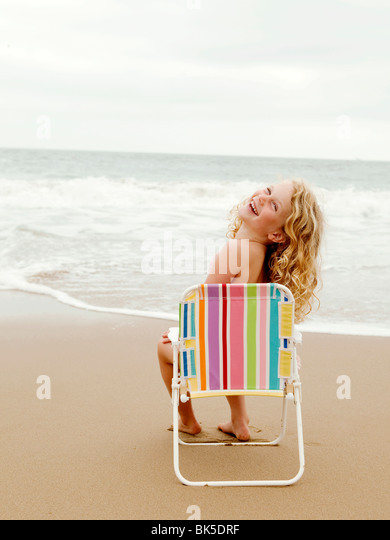 Young girl sitting on a beach chair at the beach - Stock-Bilder