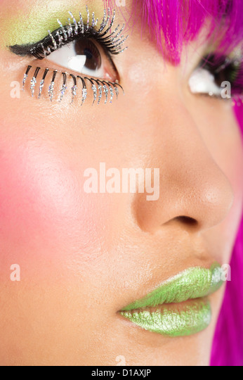 Extreme young funky woman's face false eyelashes green lipstick - Stock Image