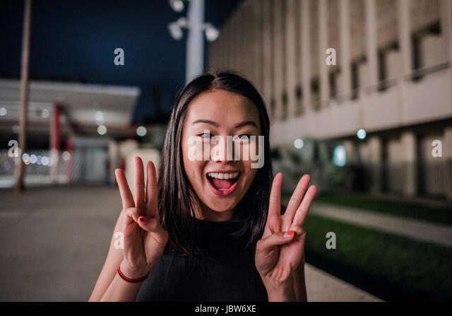 Portrait of young woman making wow hand gesture outside Los Angeles County Museum of Art at night - Stock-Bilder