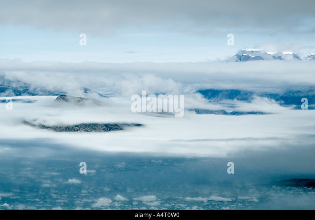 Mist clearing from the mountains, Sermilik Fjord, East Greenland - Stock Image