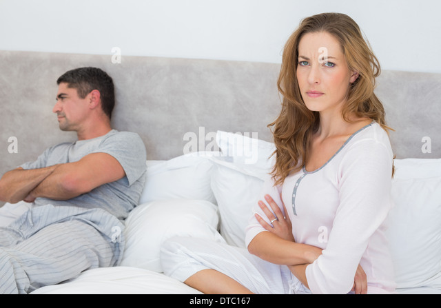 Angry woman with man in bed - Stock Image