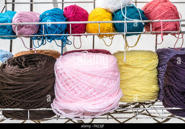 balls of wool in strikingly pure colors artistically arranged on wall shelves in canvas roofed booth at Llano park - Stock-Bilder