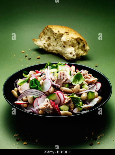 Tuna and cannellini salad, with red onion, basil, radish and cucumber server with wholegrain bread. - Stock-Bilder