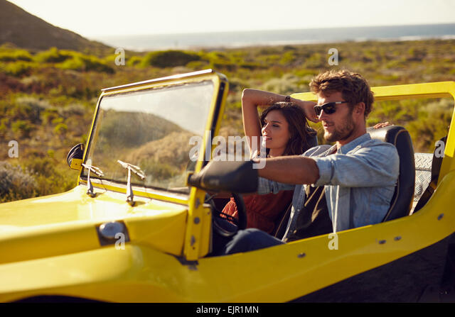 Young couple driving their car on a roadtrip. Handsome young man with his girlfriend on a holiday. Couple on a long - Stock Image