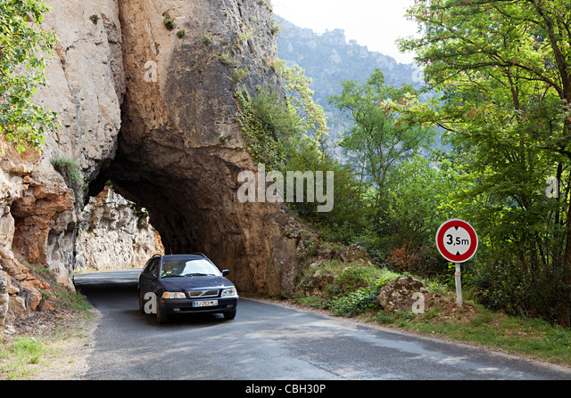 Car driving through tunnel in rock with height restriction on road down the Gorges du Tarn France - Stock Image