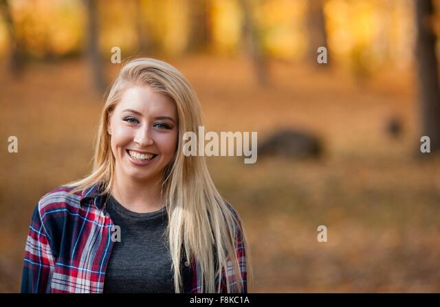 Head and shoulder portrait of young woman with long blond hair in autumn forest - Stock-Bilder
