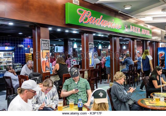 Miami Florida MIA Miami International Airport Brew House Budweiser restaurant brewery bar beer man woman smartphone - Stock Image