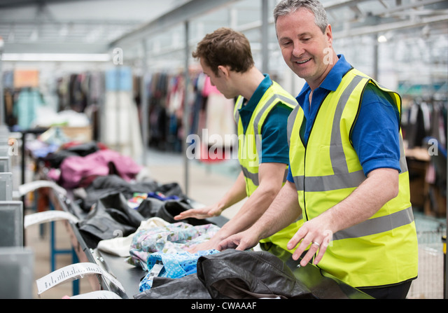 Two men sorting clothes on conveyor belt in warehouse - Stock Image