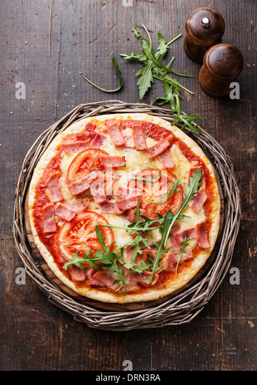 Italian pizza with ham and arugula leaves on wooden table - Stock Image