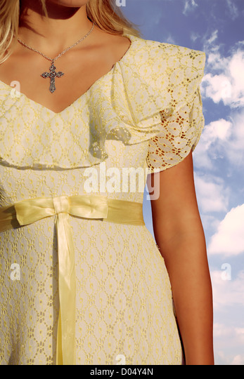 close-up of a woman in a yellow dress with a crucifix - Stock Image