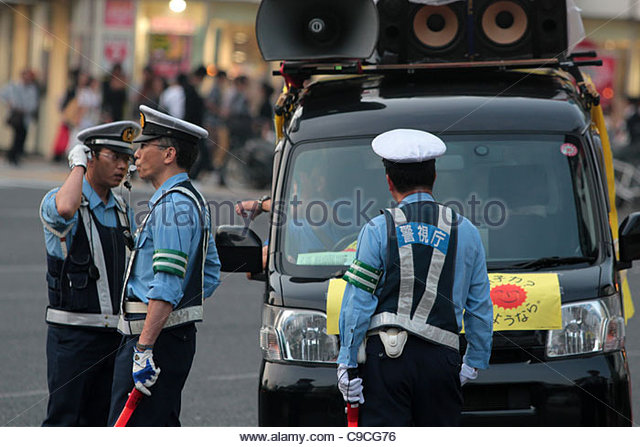 A protest van is stopped by police during an anti-nuclear rally in Shinjuku, Tokyo. - Stock Image