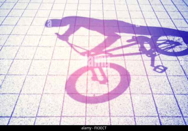 Retro toned blurred shadow of a teenager riding a bmx bike. - Stock-Bilder