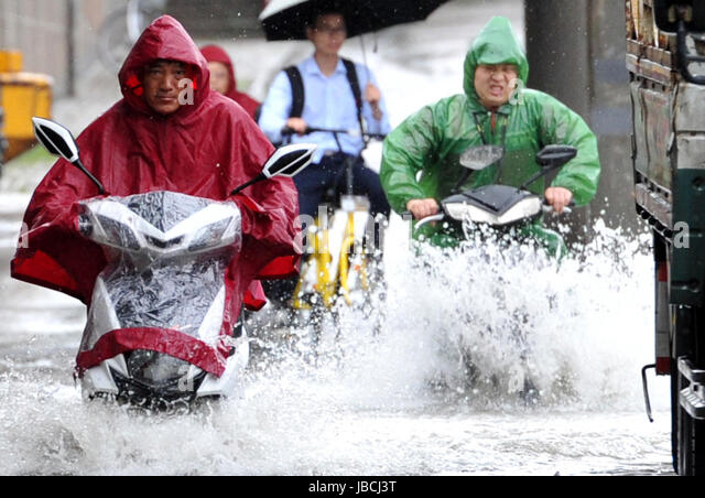 Nanjing, China's Jiangsu Province. 10th June, 2017. Citizens ride on a flooded street in Nanjing, capital of - Stock-Bilder