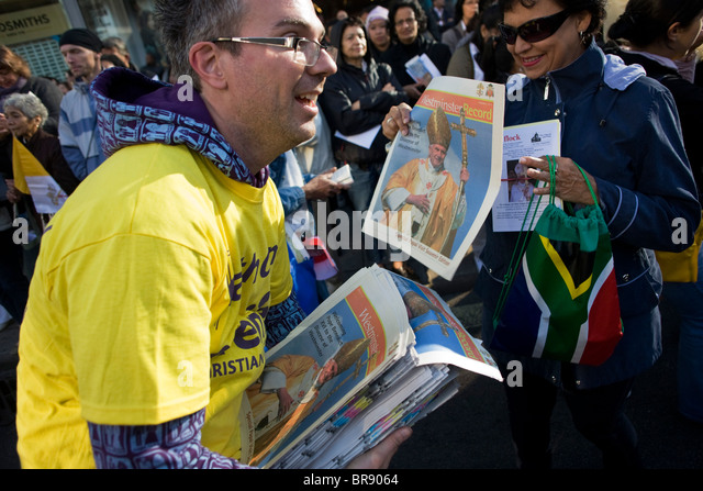 Catholics read free newspapers to crowds outside Westminster Cathedral before Pope Benedict XVI arrives - Stock-Bilder